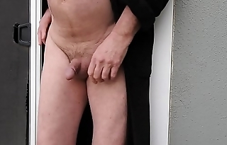 A man in a robe putting his cock in a screen hole and peeing.